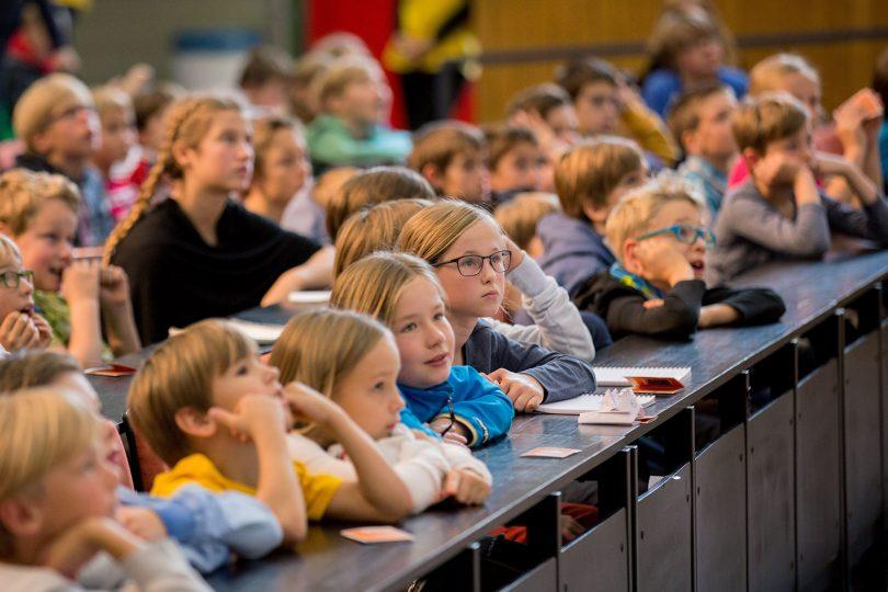 Zu sehen sind Kinder, die eine Kinder-Uni-Vorlesung aus dem letzten Jahr besuchen.