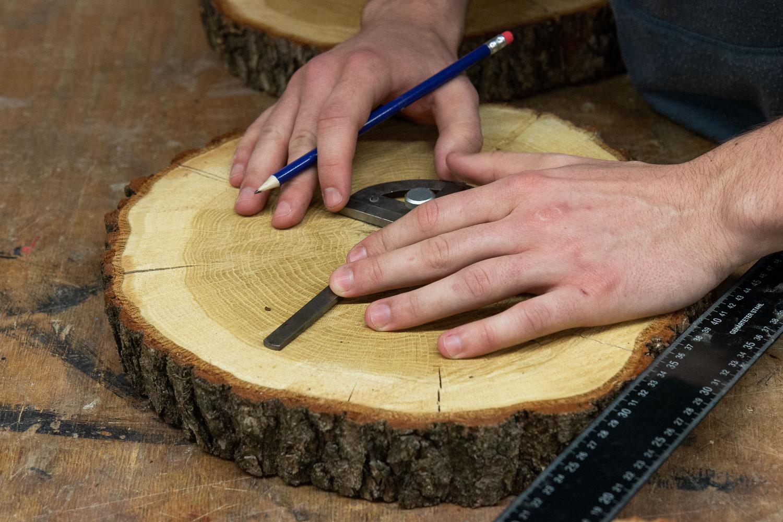 Maschinenbau-Student Vincent Friesen misst eines seiner drei Holzstücke für die weitere Verarbeitung aus. Bildnachweis: Markus Hörster/TU Braunschweig
