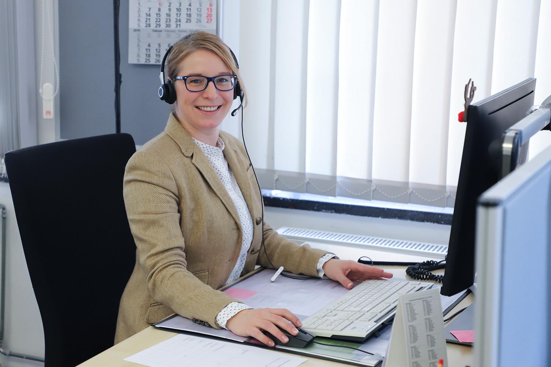 Zu sehen ist eine Mitarbeiterin vom Studienservice-Call mit Headset an ihrem Arbeitsplatz.