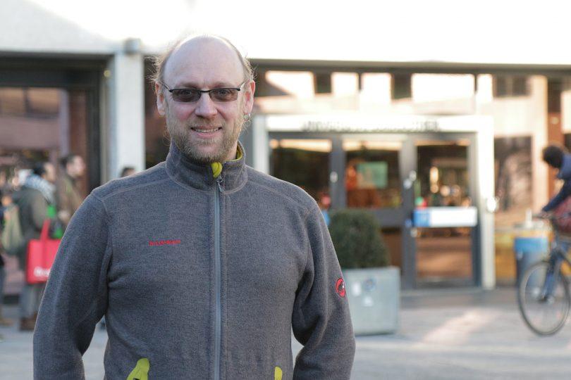 Zu sehen ist Carsten Elsner vor der Universitätsbibliothek.