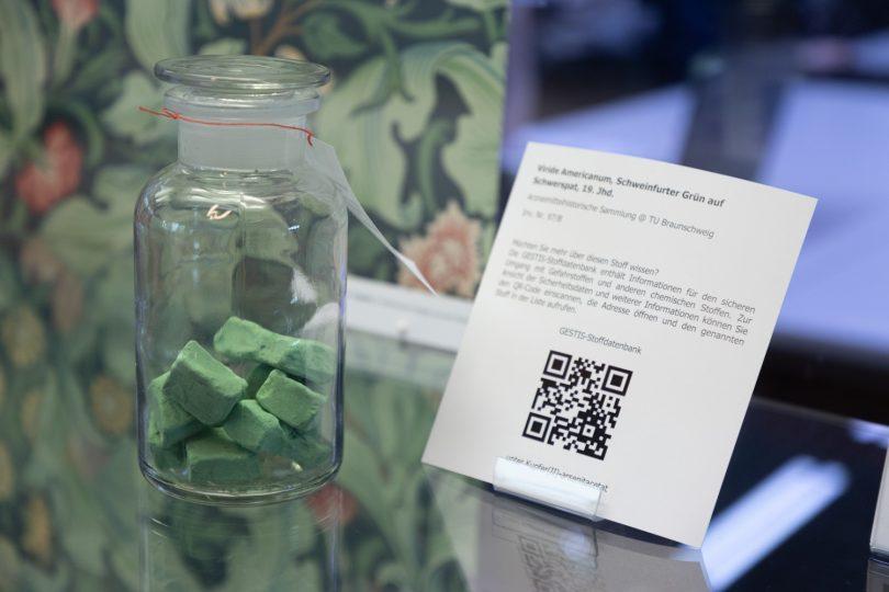 Glas mit grüner Substanz vor einer grüngrundigen Tapete.