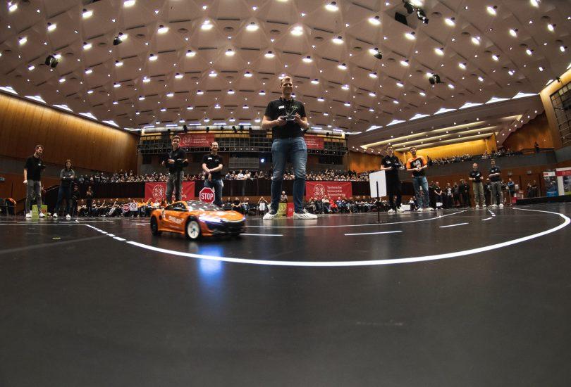 Blick in die zuschauerränge der Stadthalle aus der Perspektive eines der Modellfahrzeuge im Carolo-Cup