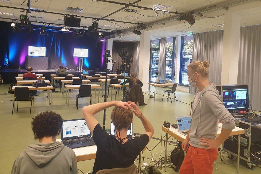 Blick über den leeren Raum vor der Bühne, über die Schulter von drei Technikern