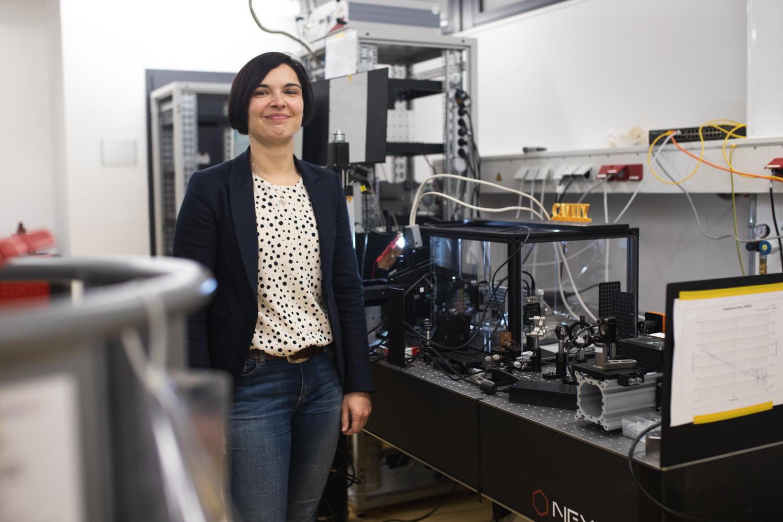 Professorin Stefanie Kroker steht vor ihrem Laboraufbau, an dem sie optische Bauteile für den Quantencomputer des QVLS entwickelt.