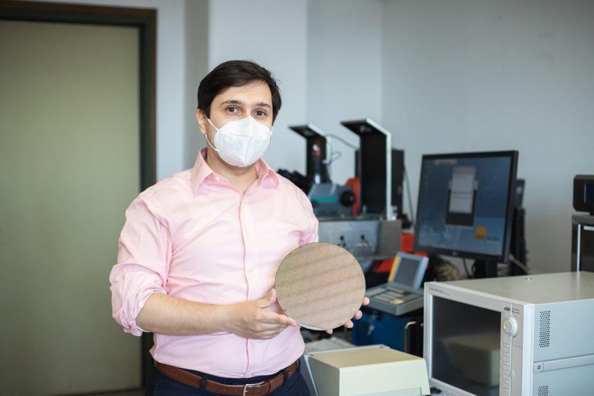 Professor Vadim Issakov mit einem kreisrunden, etwa einen Millimeter dünnen Wafer. Die Scheibe ist die Grundplatte für die Chip-Produktion.
