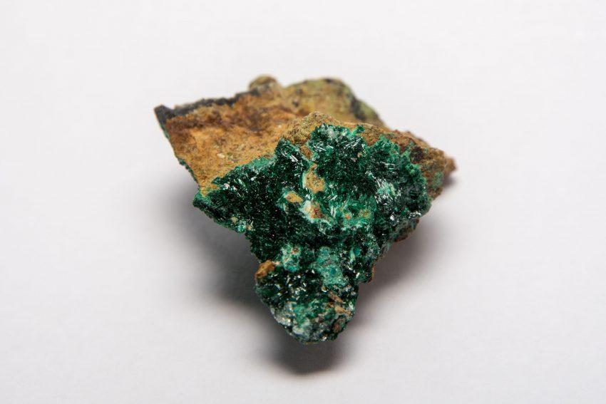 Ein kleiner Stein mit einer dünnen Schicht grüner Atacamit-Kristalle auf der Oberfläche