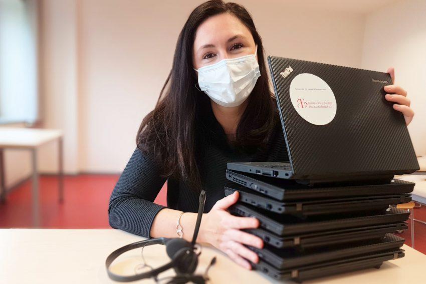 Frau mit Maske vor einem Stapel Laptops