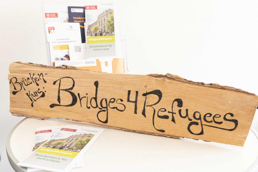 """Schriftzug """"Bridges4Refugees"""" auf Holzbrett mit Flyern"""