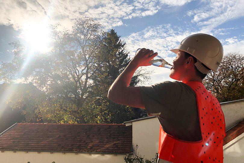 Ein Bauarbeiter mit Helm und Warnweste trinkt aus einer Wasserflasche.