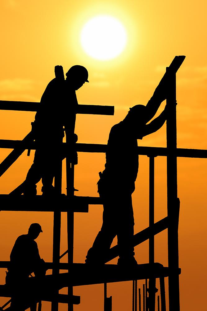 Bauarbeiter auf einem Gerüst in der Abendsonne.