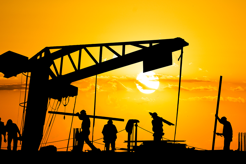 Bauarbeiter auf einer Baustelle im Licht der untergehenden Sonne.