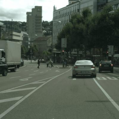 Der Blick aus Perspektive des Fahrendens auf eine mehrspurige Straße. Zu sehen sind mehrere parkende und fahrende Autos, sowie eine rote Ampel, an der Fußgänger*innen kreuzen.